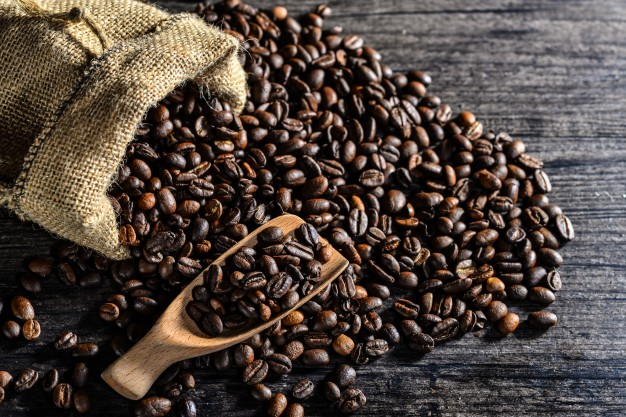 top-view-of-wooden-spoon-and-a-canvas-bag-of-coffee-beans_1112-441